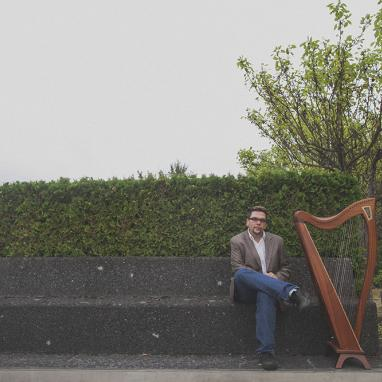 Man sits on outdoor stone bench next to a harp
