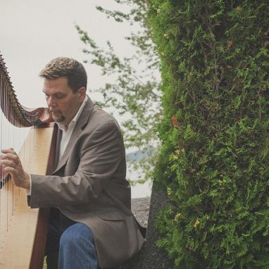 Man plays harp next to a hedge