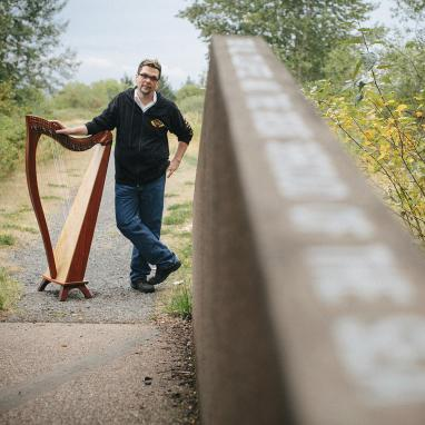 man stands at the end of blurry bridge next to harp