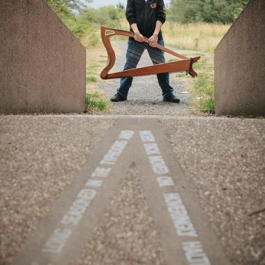 man stands at far end of blurry bridge holding harp looking to the side