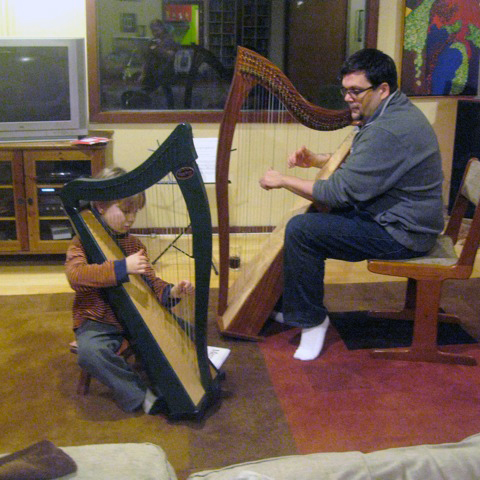 Man sits with harp facing a small boy with a harp